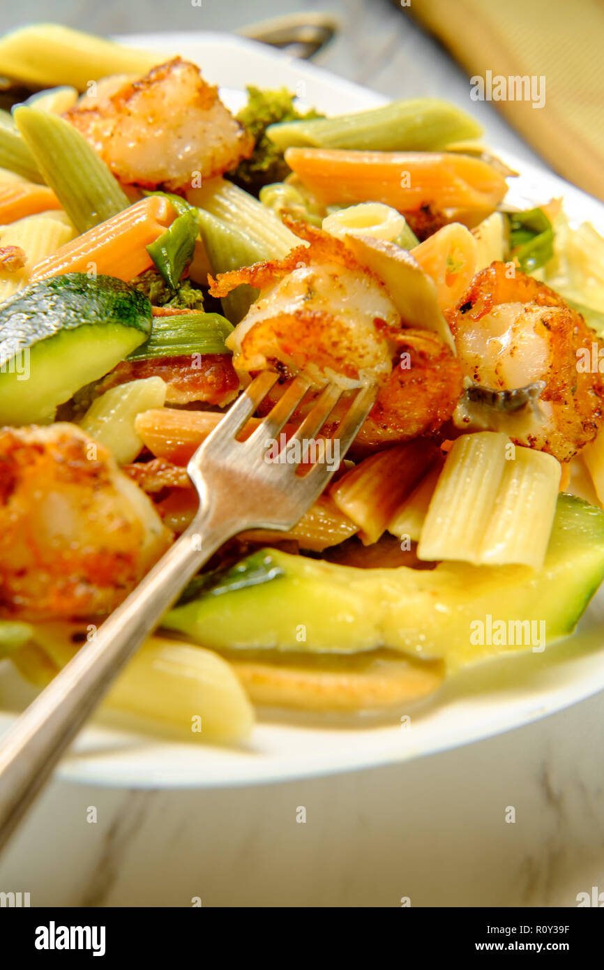 Shrimp primavera with tricolor penne in a white wine sauce - Stock Image