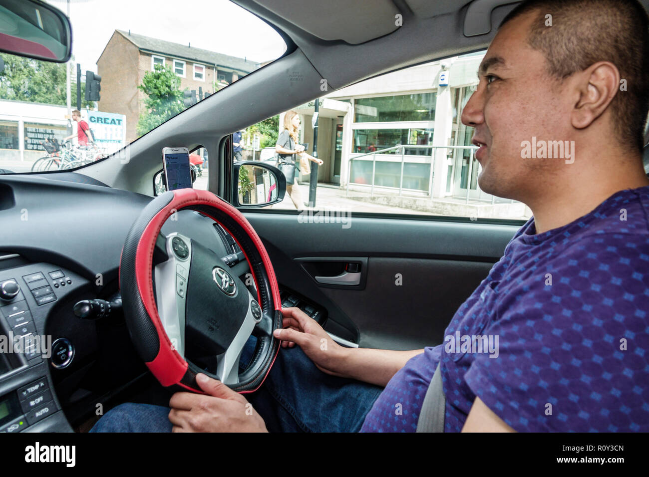 London England United Kingdom Great Britain Lambeth South Bank uber driver driving car interior steering wheel Asian man right-hand drive system Toyot - Stock Image