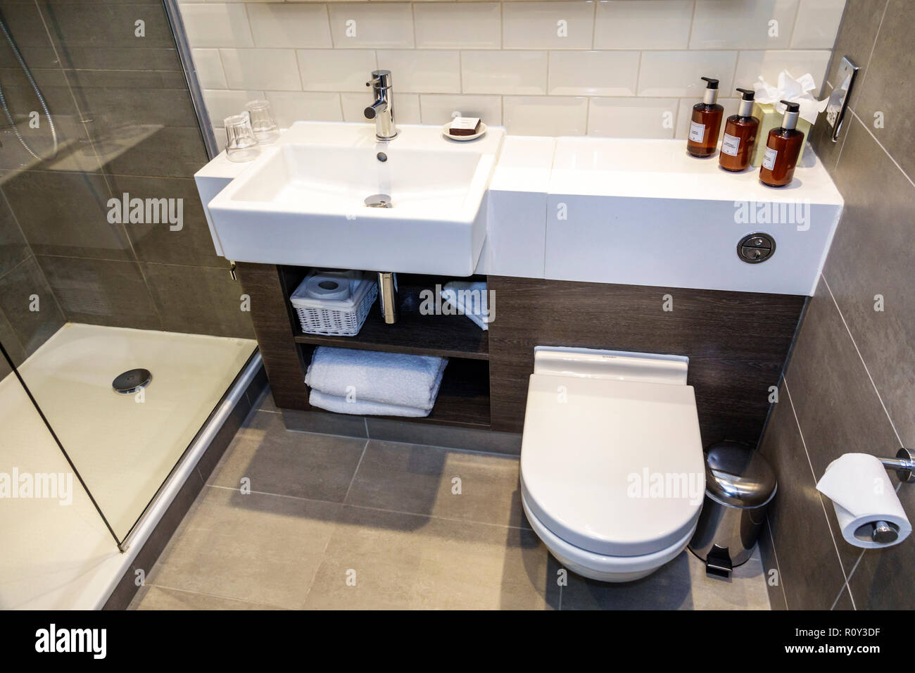 London England United Kingdom Great Britain Lambeth Staybridge Suites London Vauxhall hotel guest bathroom vanity sink toilet loo shower - Stock Image