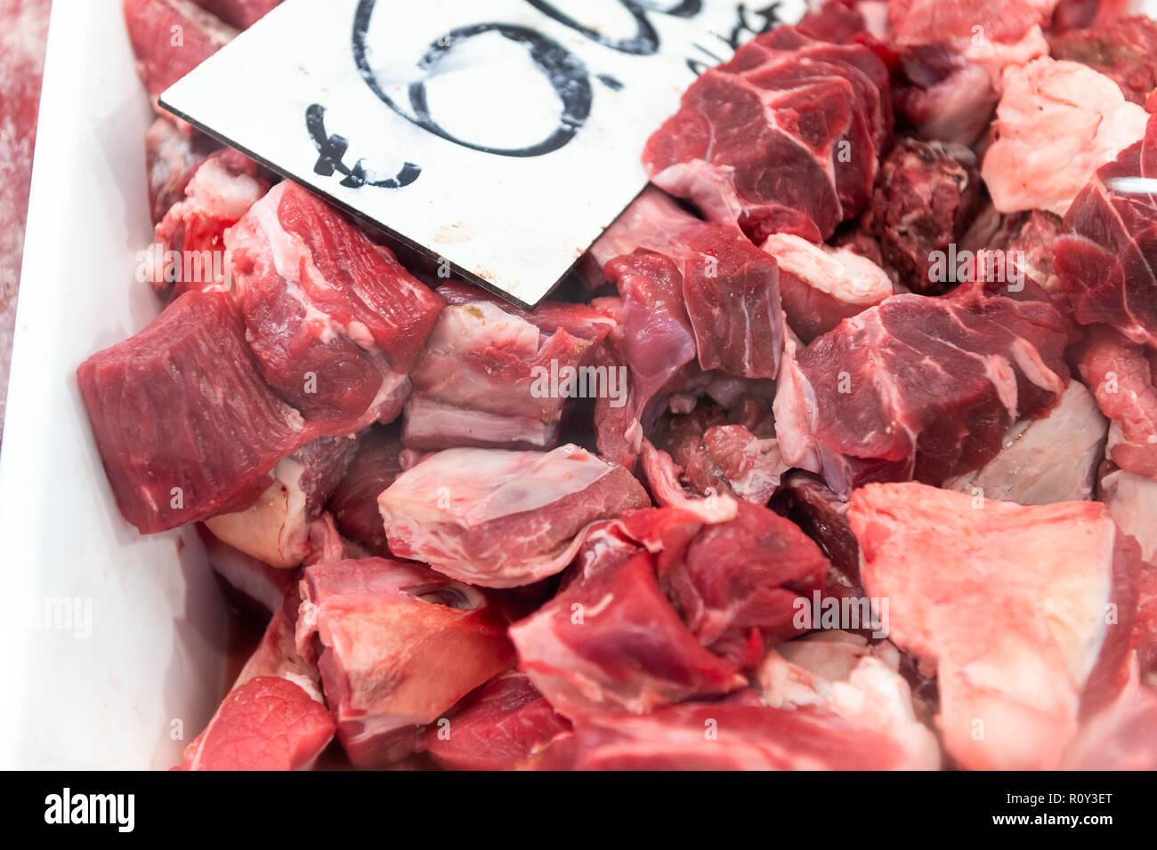 Closeup of many beef meat chunks, cut in slices on retail display store, shop in butchers shopping area in fridge, refrigerated with price tag, label - Stock Image