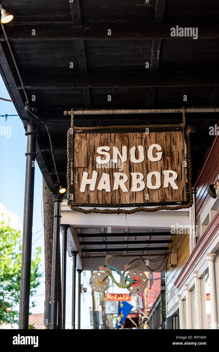 New Orleans, USA - April 22, 2018: Frenchmen street covered sidewalk in Louisiana town, city, building, sign closeup for Snug Harbor Jazz Bistro - Stock Image