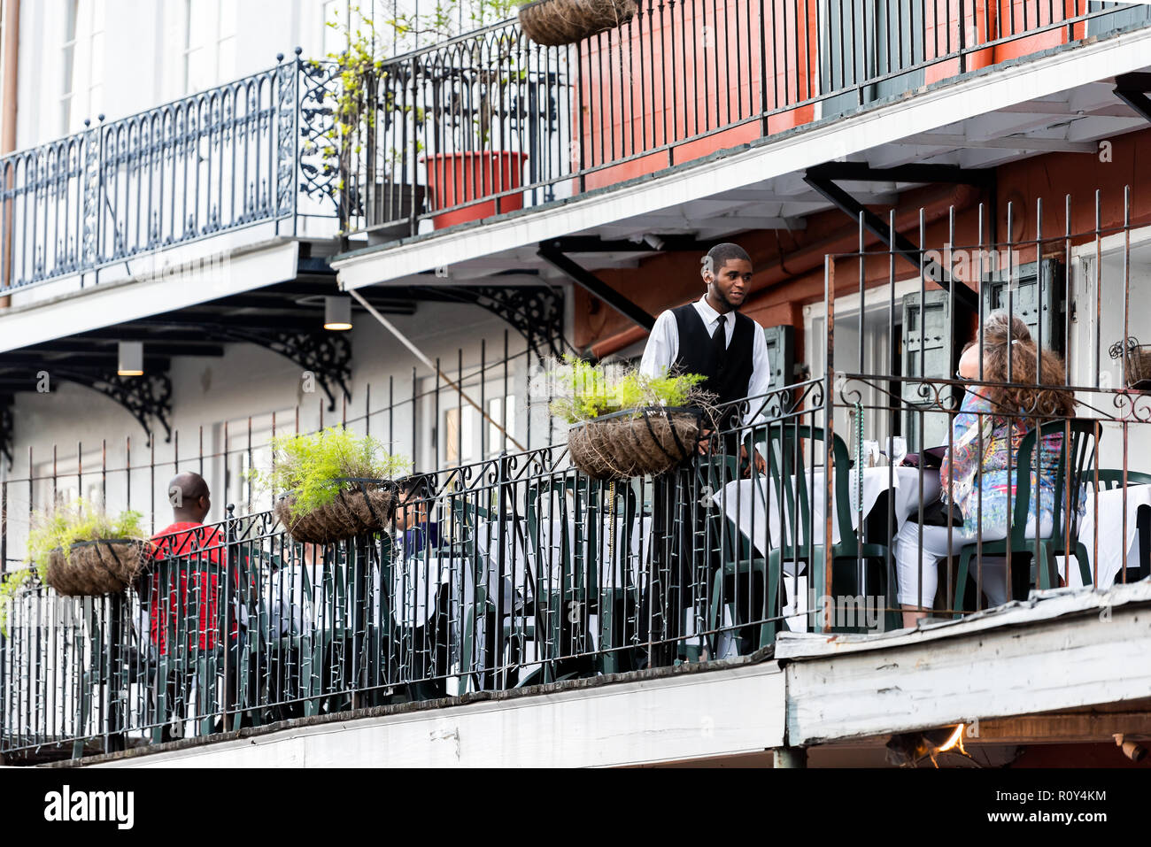 New Orleans, USA - April 22, 2018: Old town Bourbon Decatur street in Louisiana town, city, cast iron balcony building, waiter, people sitting in rest - Stock Image