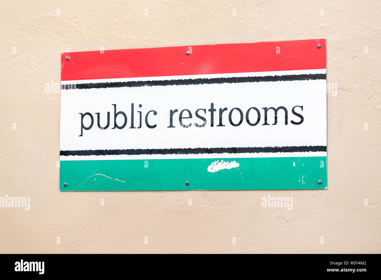 Restrooms bathroom Italian flag sign on building wall on sidewalk closeup in town, city, nobody, architecture, symbol - Stock Image
