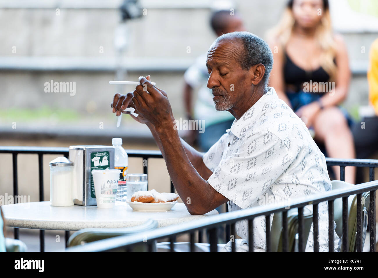 New Orleans, USA - April 22, 2018: Man sitting at table at famous, iconic Cafe Du Monde shop, restaurant eating beignet powdered sugar donuts, coffee, Stock Photo