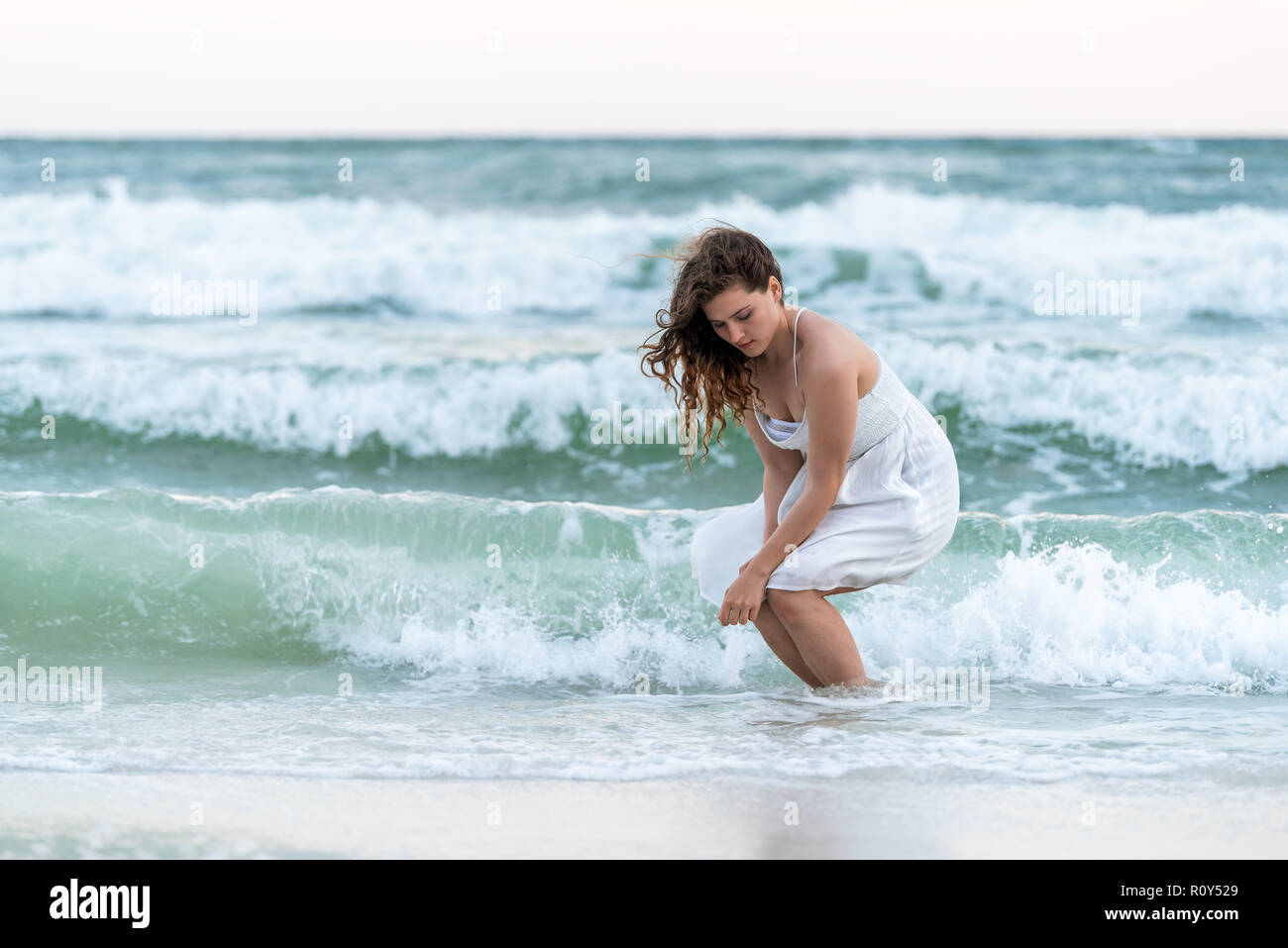 Young woman sitting squatting in white dress on beach sunset in Florida panhandle with wind, ocean waves crashing legs, tan skin, looking down - Stock Image