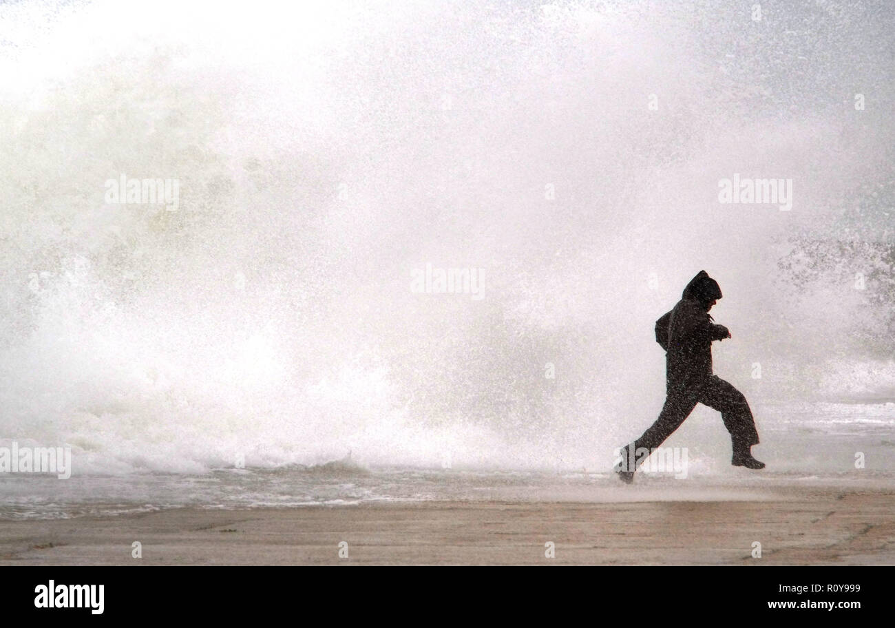 Newhaven, East Sussex. UK. 7th November 2018. A man risks his life dodging huge waves in Newhaven Harbour, East Sussex, as strong winds whip up the seas at high tide. © Peter Cripps/Alamy Live News - Stock Image