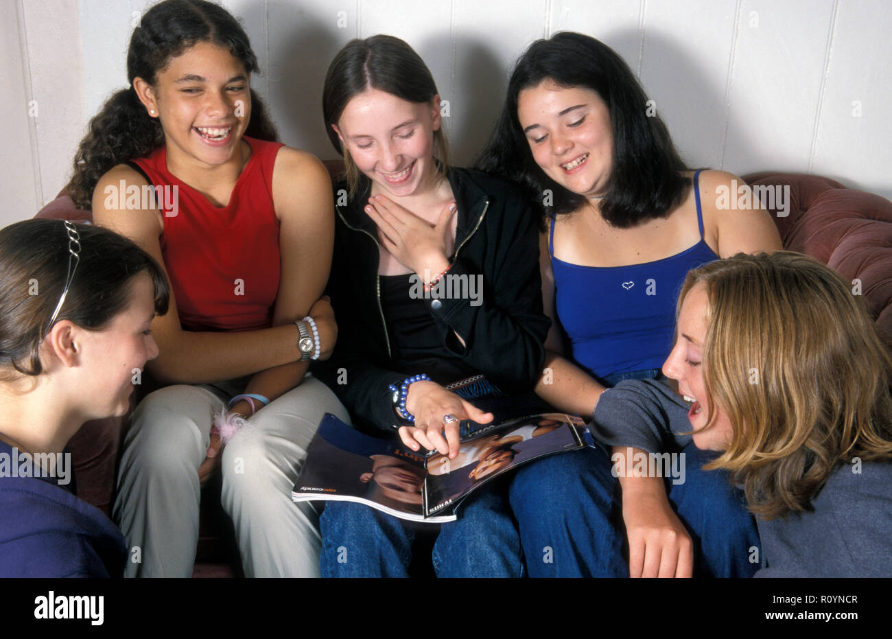 group of teenage girls having a laugh over a magazine article Stock Photo