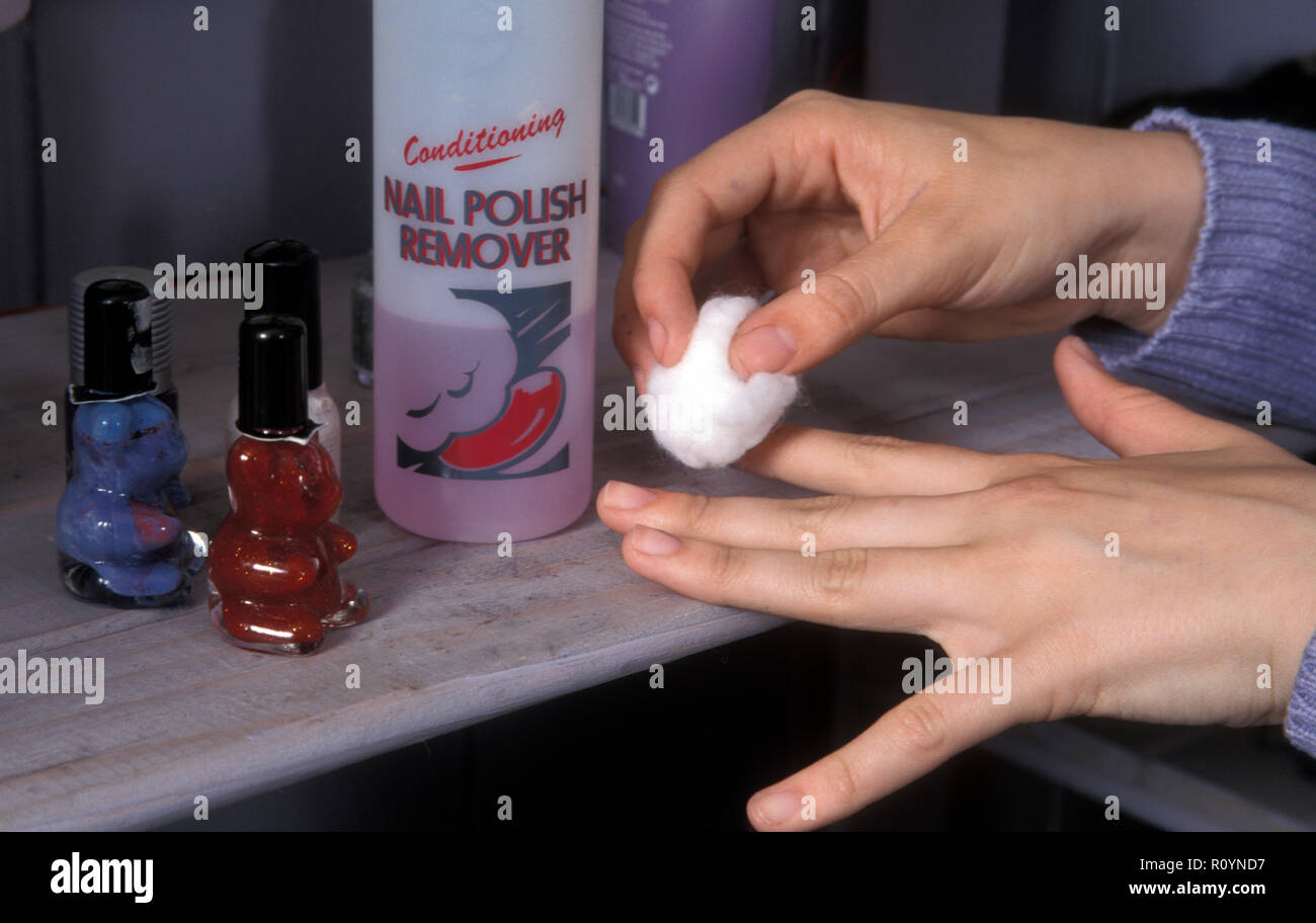 young girl applying nail polish remover Stock Photo