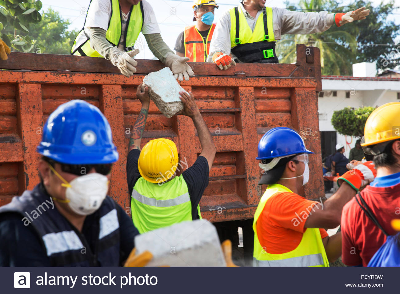 Teams of volunteers clear rocks and rubble after the small Mexican town of Jojutla was hit by a huge earthquake. - Stock Image