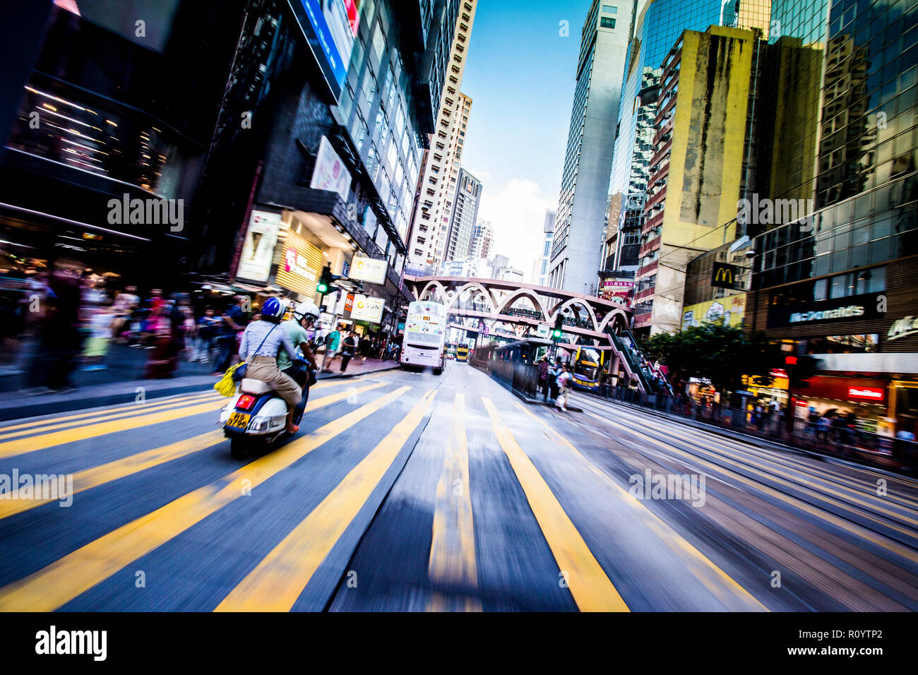 A Vespa passes the crosswalk in the busy shopping area of Causeway Bay, Hong Kong. - Stock Image