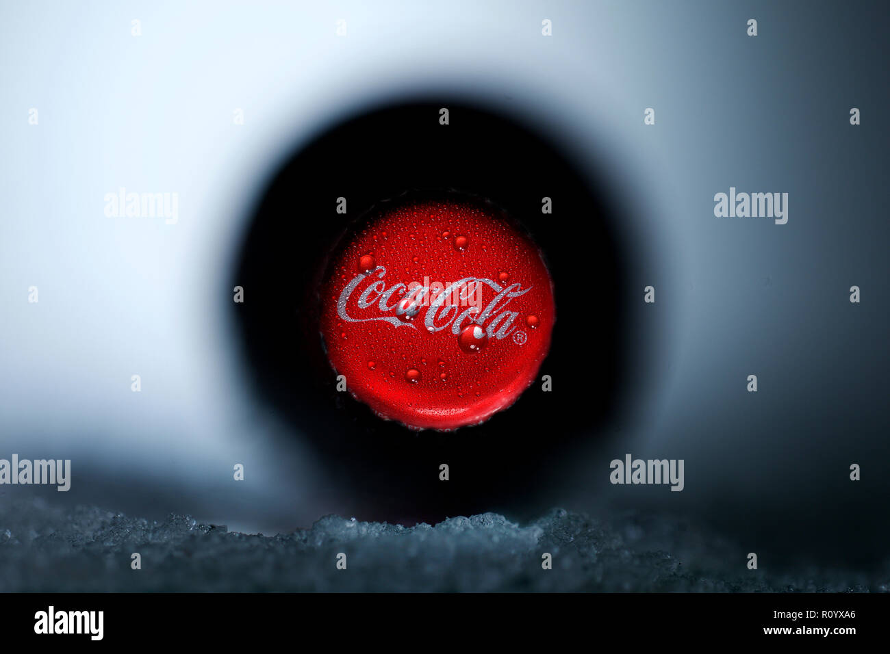 Coca-cola bottle in freezer compartment, shallow focus close up on red bottle top - Stock Image