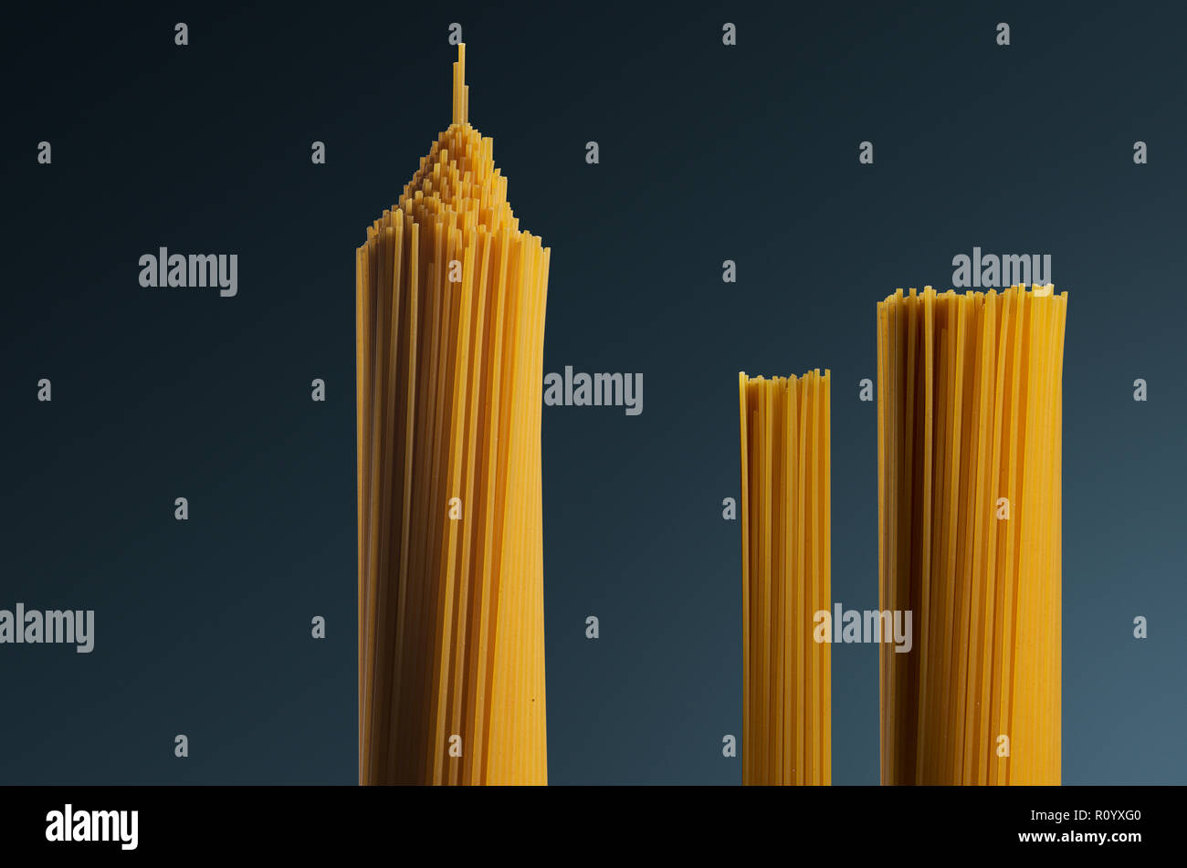 Three bunches of raw uncooked spaghetti shaped as tower structures against grey background - Stock Image