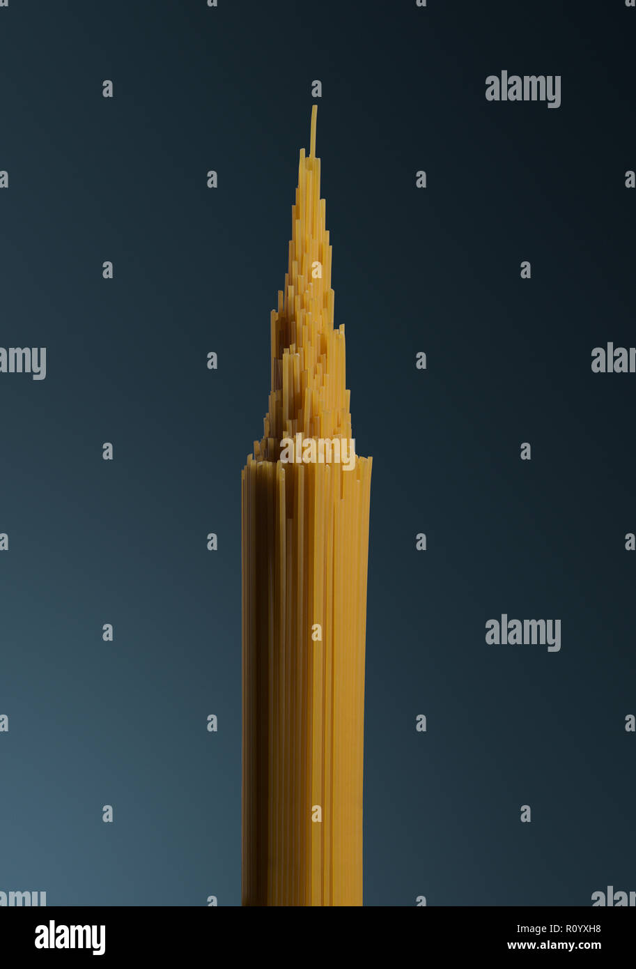 Bunch of raw uncooked spaghetti shaped as pointed tower structure, Empire State Building - Stock Image