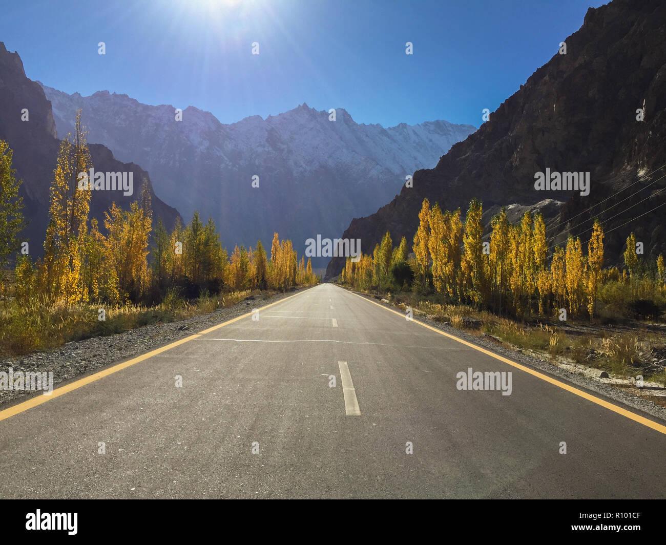 Sunrise with clear blue sky over Karakoram highway. Poplar trees get brilliant golden leaves. Passu, Pakistan. - Stock Image