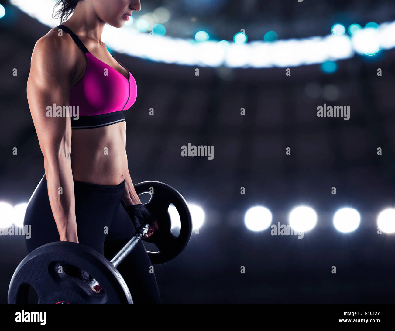 Athletic woman training biceps at the gym - Stock Image