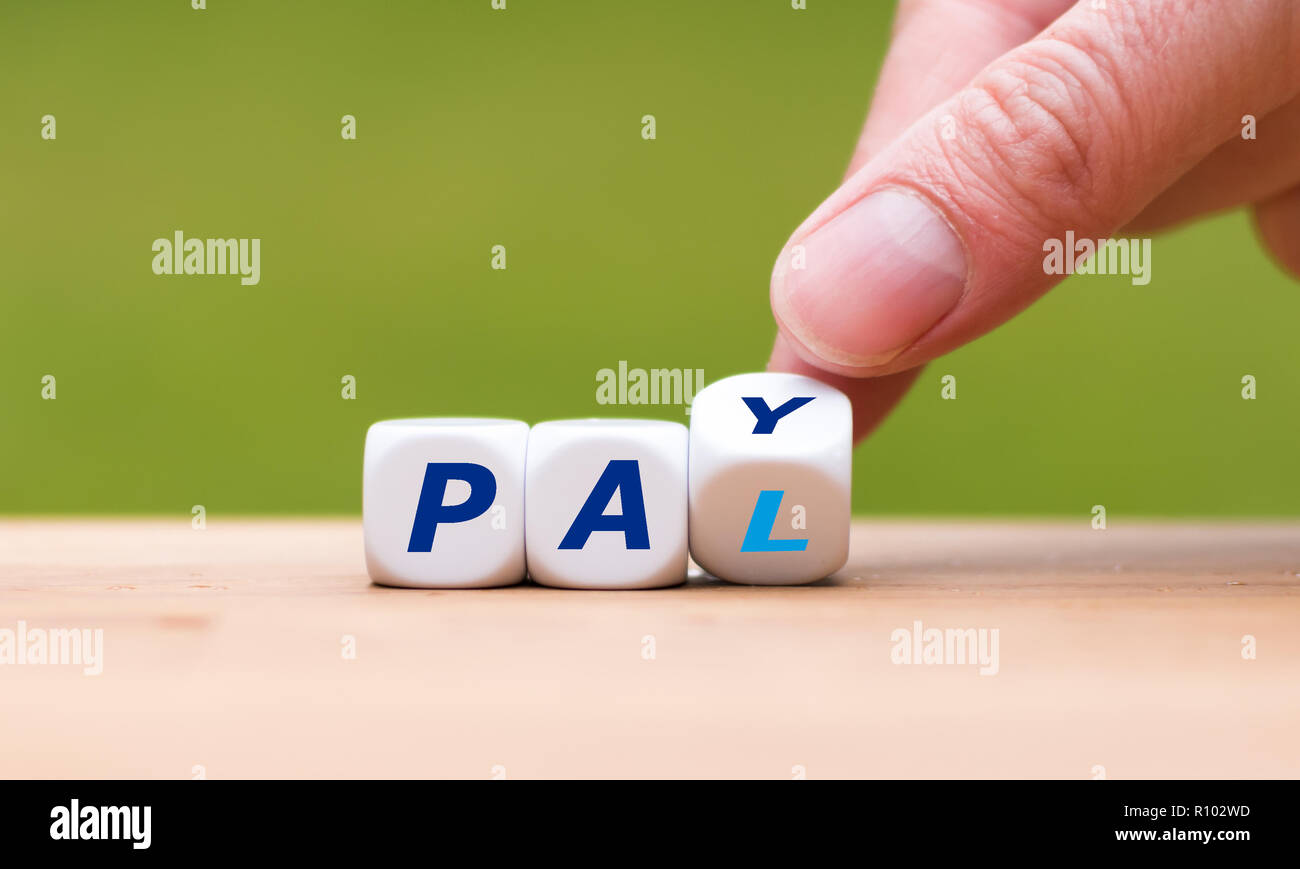 hand is turning a dice and changes the word pay to pal stock