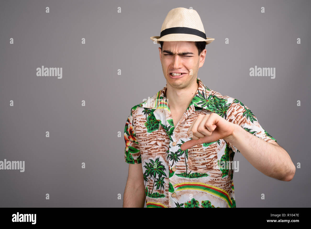 Young handsome tourist man ready for vacation against gray backg - Stock Image