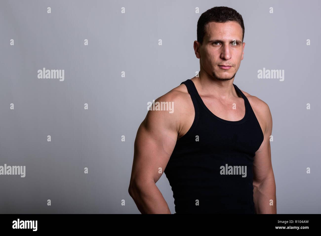 Studio shot of young muscular Persian man wearing sleeveless aga - Stock Image