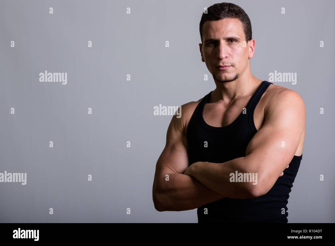 Studio shot of young muscular Persian man wearing sleeveless wit - Stock Image