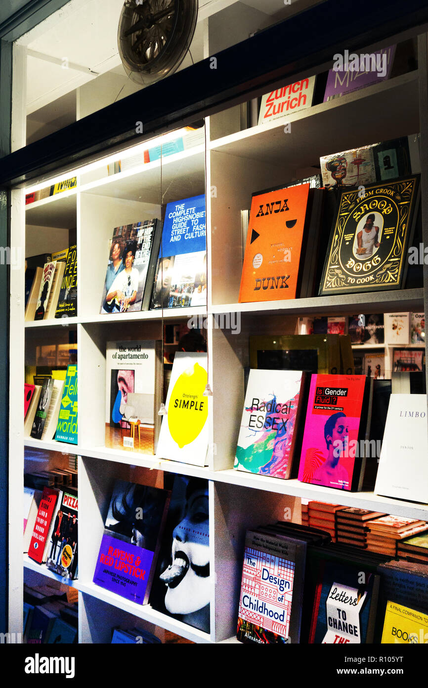 Collection of books on shelves in bookshop window. - Stock Image