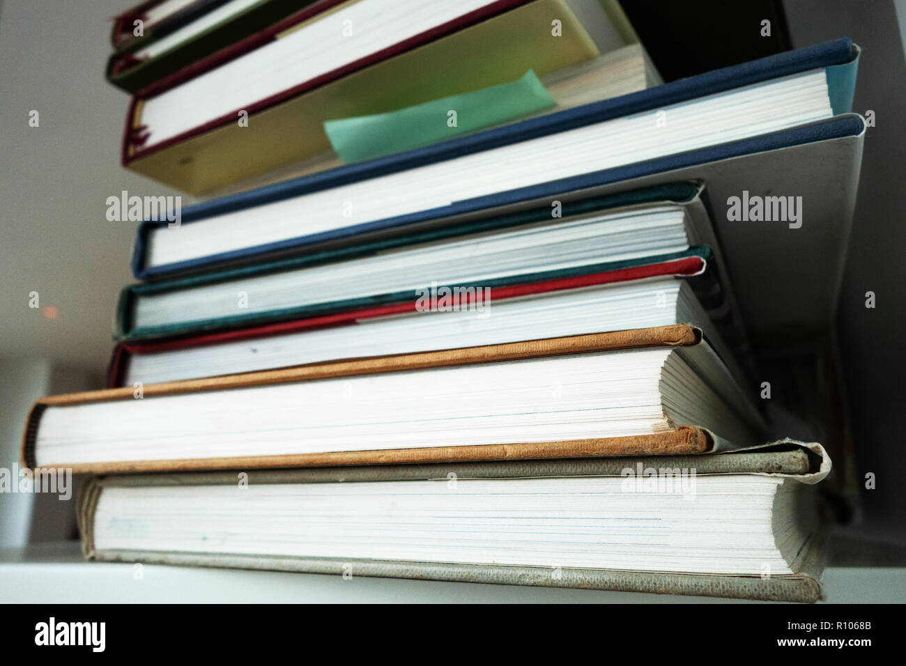 photograph of the sides of a pile of hardbacked books on a white shelf, no copy - Stock Image