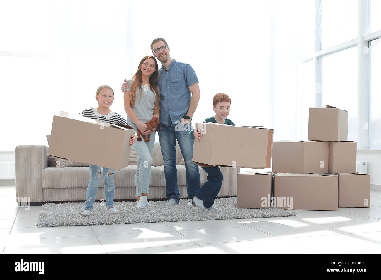 family moves the boxes to a new apartment. - Stock Image
