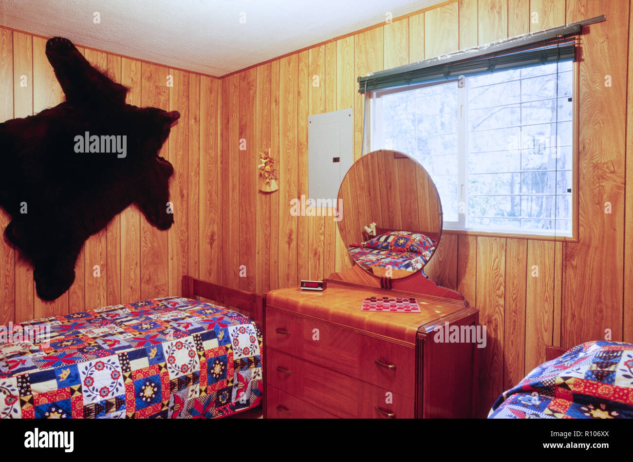 Rustic Cabin Bedroom with a Bear Skin on the wall, SD, USA - Stock Image