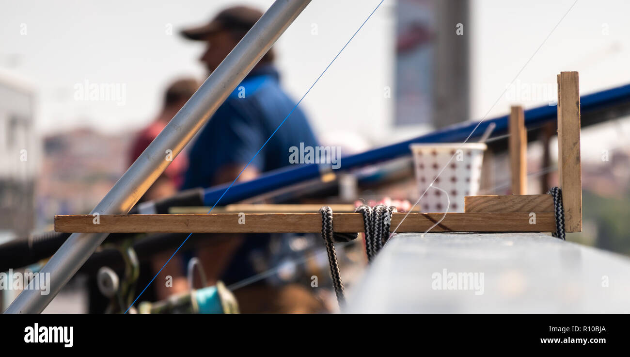 Tricky and ingenious invention for attaching a fishing rod to the railing of a bridge - Stock Image