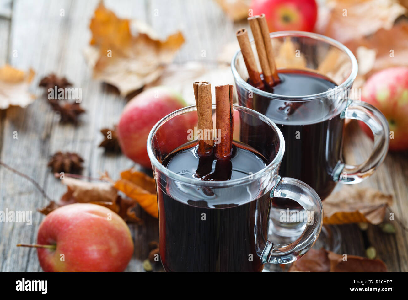 Hot mulled wine in glass on wooden table Stock Photo
