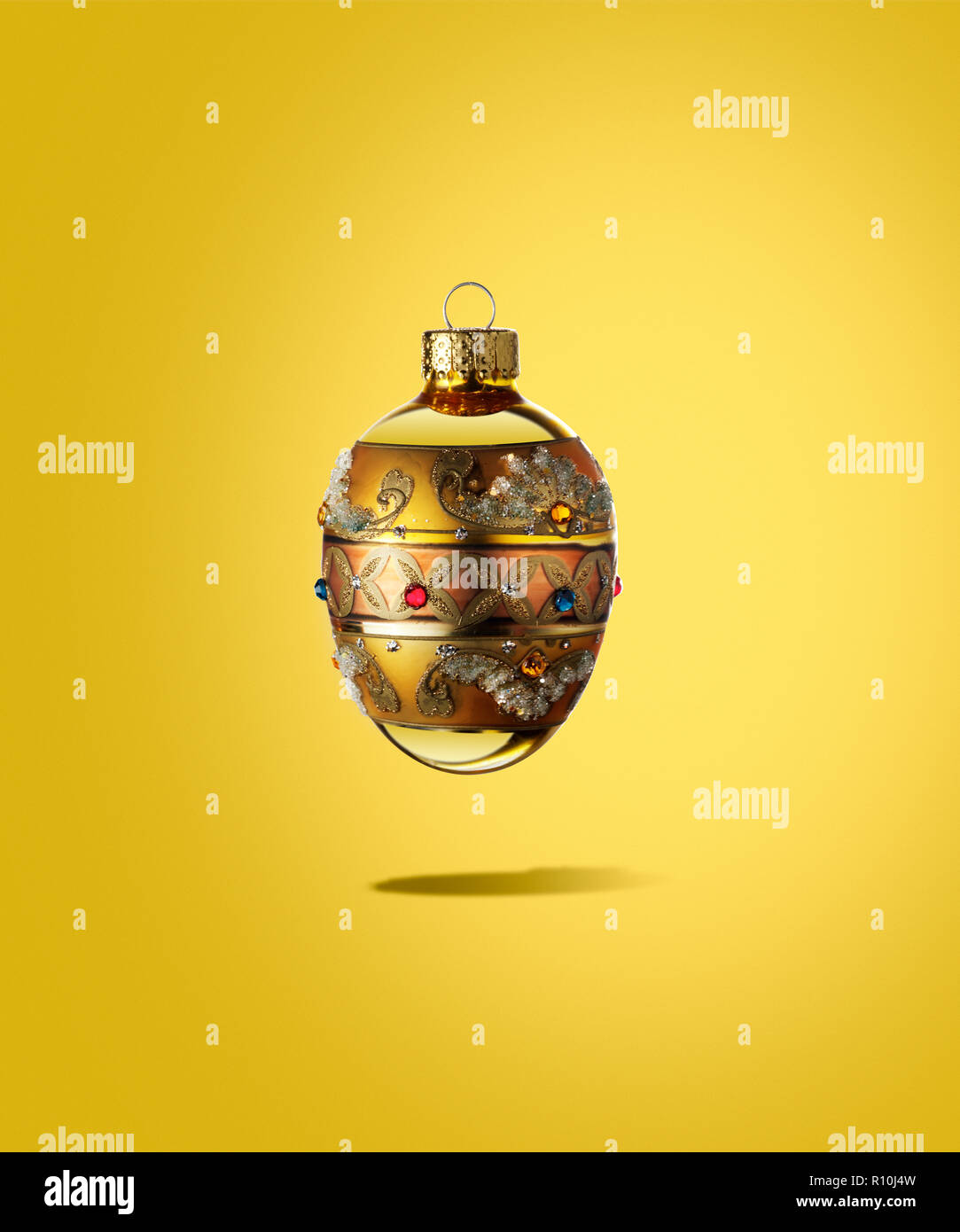 Close Up Of Regal Christmas Bauble Floating With Shadow Yellow
