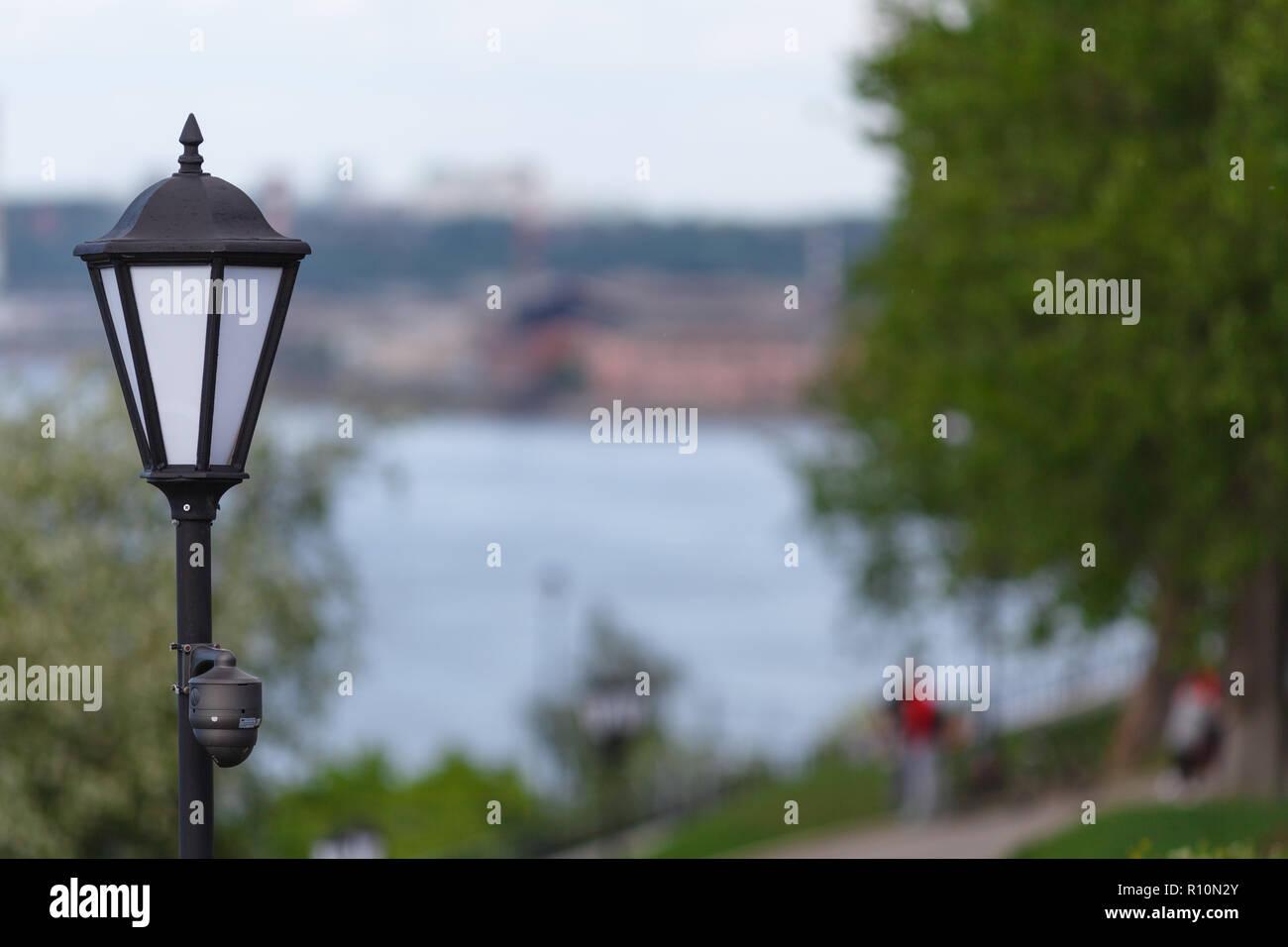 CCTV surveillance camera mounted on vintage street lantern - Stock Image