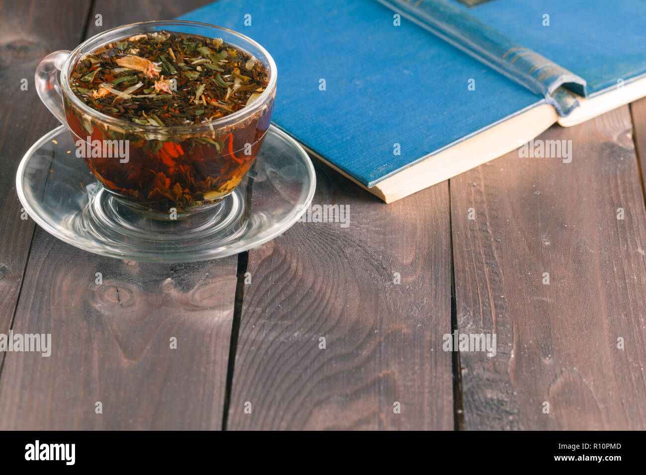 Cup of hot tea with book on table on dark background - Stock Image