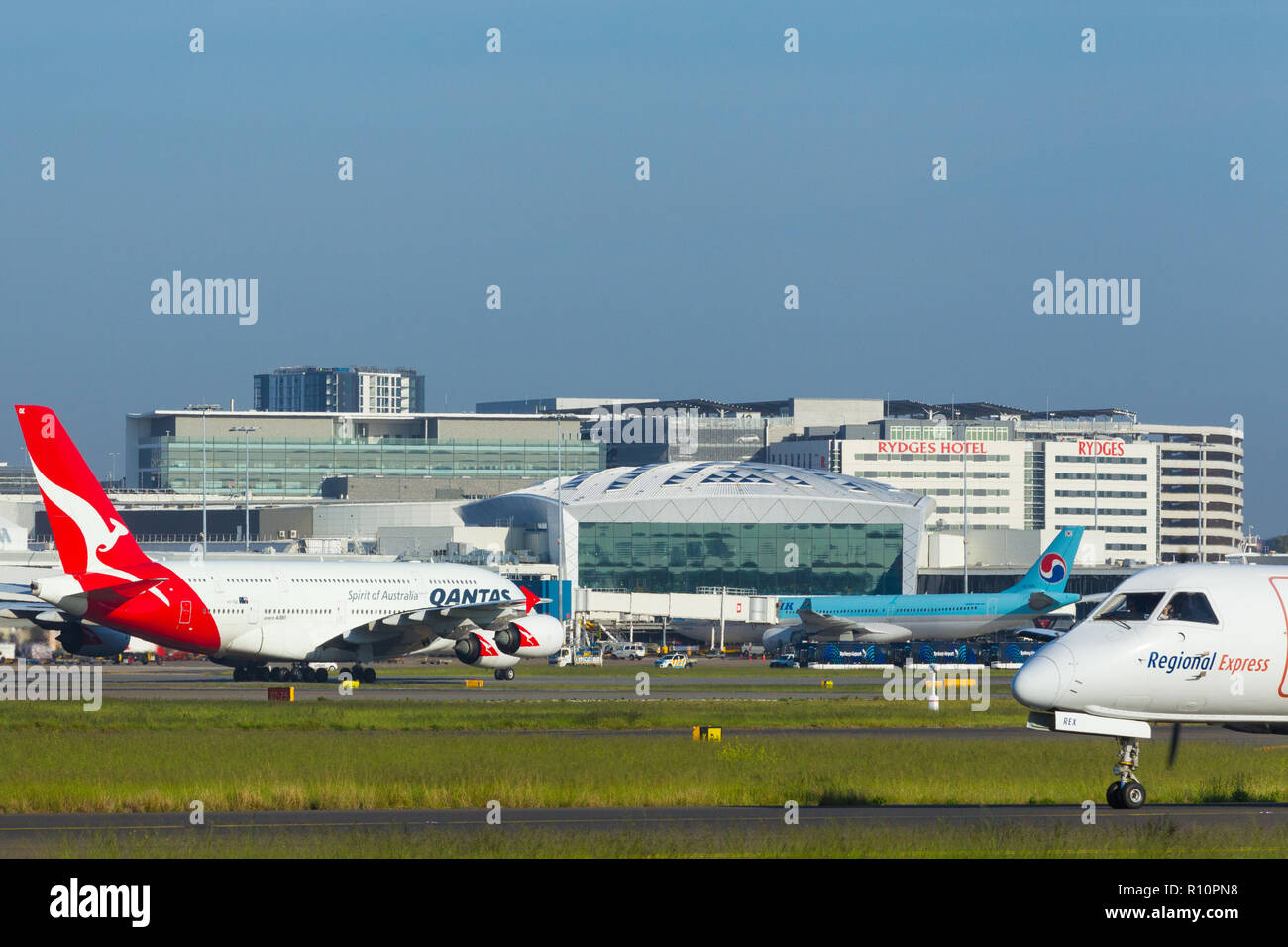 Detail from Sydney (Kingsford Smith) Airport in Sydney, Australia, looking towards the International Terminal on the western side of the airport. Pictured: a Qantas Airbus A380 (call sign VH-OQE) taxying towards the International Terminal with a REX Regional Express aircraft in the foreground. - Stock Image