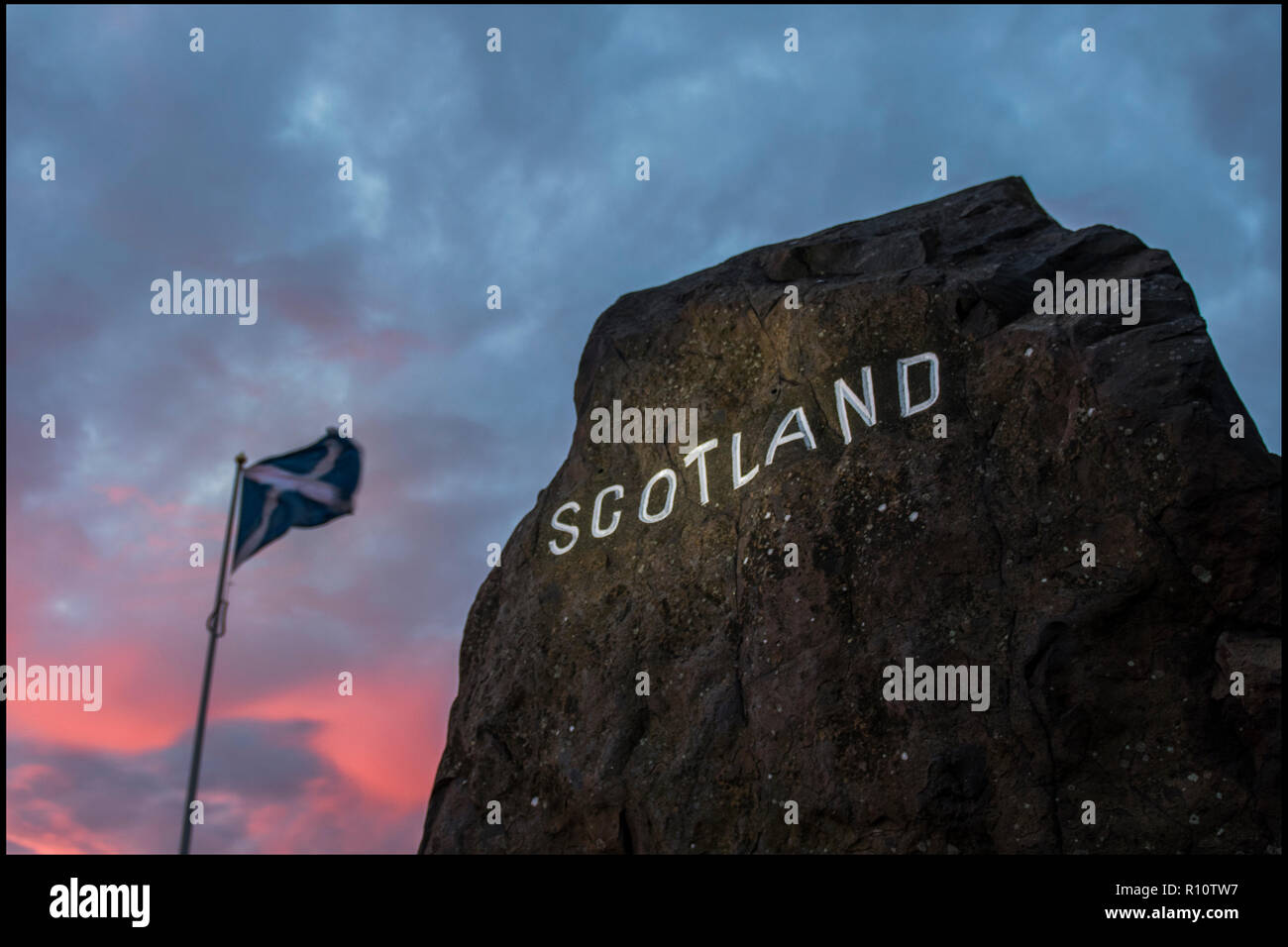 The large rock  with Scotland engraved and painted in white, which marks the border between Scotland and England at the Carter Bar. - Stock Image