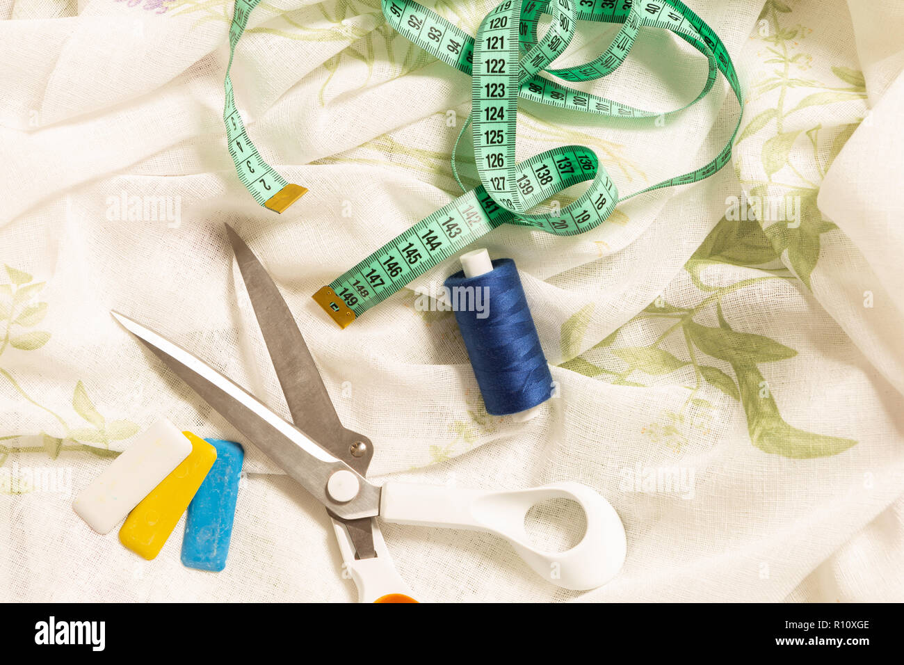 Sewing articles such as scissors thread chalk and measuring tape on fabric for curtain - Stock Image