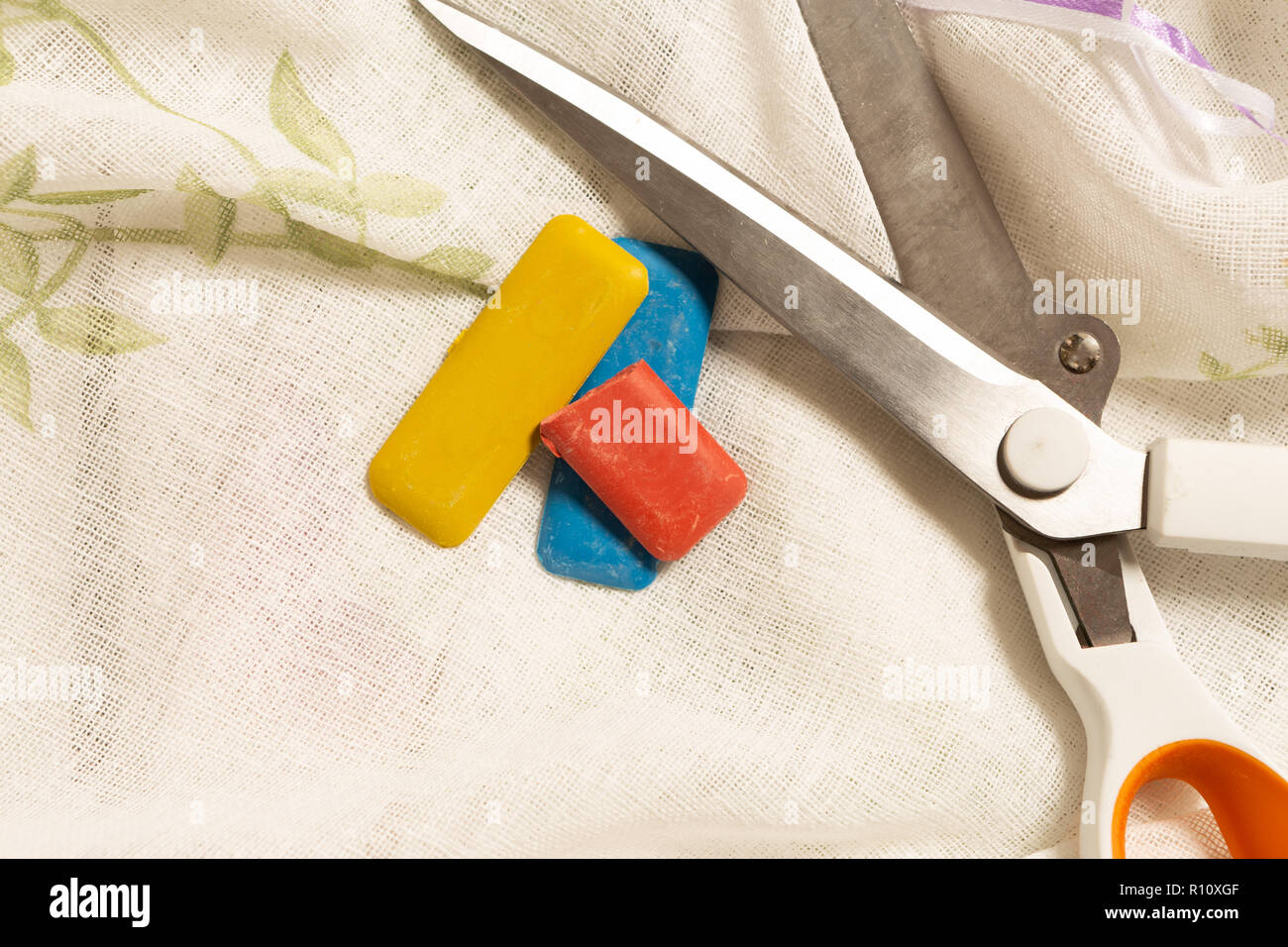 Scissors and colourful tailor chalk on white curtain fabric as diy concept - Stock Image