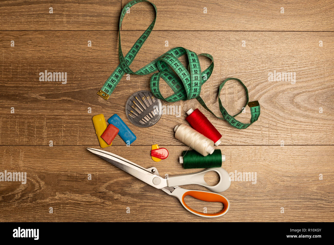 Scissors, needles, thread, chalk, measuring tape as sewing equipment on wooden work bench - Stock Image