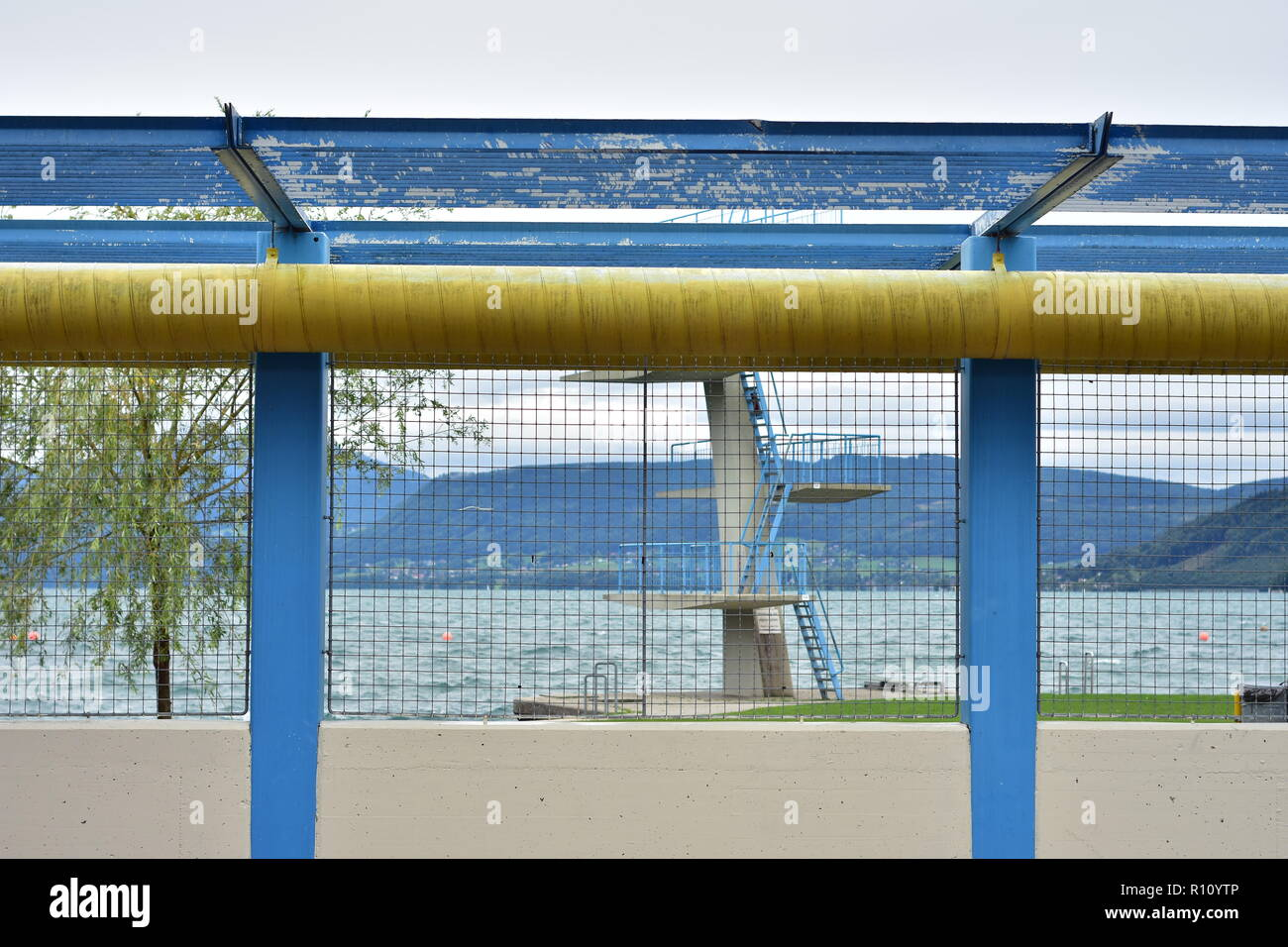 Concrete diving tower with metal staircase and railing behind wire fence on shore of lake Mondsee. - Stock Image