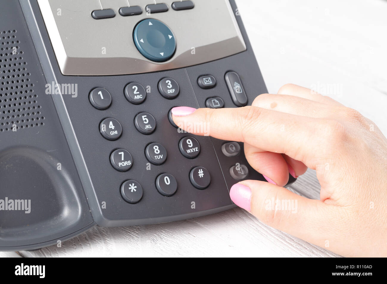 dialing voip phone in the office, keyboard and monitor detail in the background - Stock Image