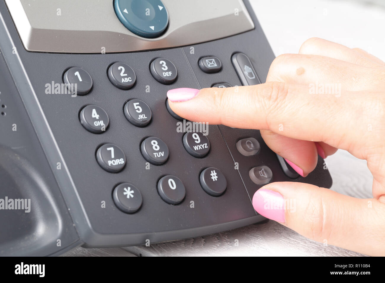 Close up of Finger dialing to make a phone call in office - Stock Image