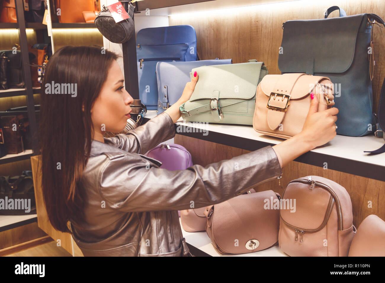 Female customer purchasing new handbag in shop - Stock Image
