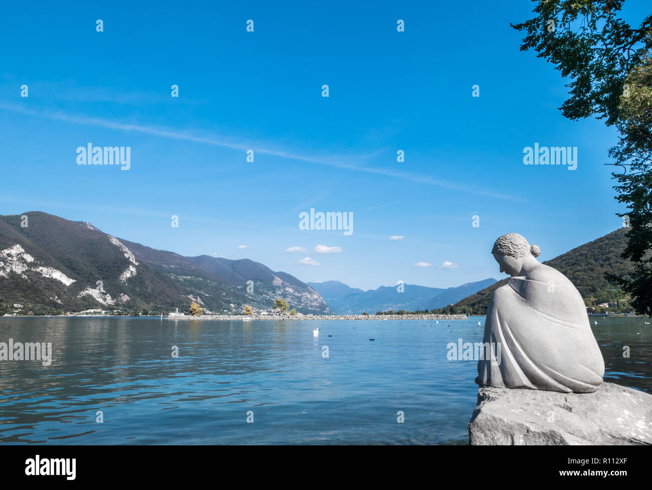 Sculpture of a young woman sitting on a rock, on the shore of Lake Iseo. In the background, the lake and the mountains. - Stock Image