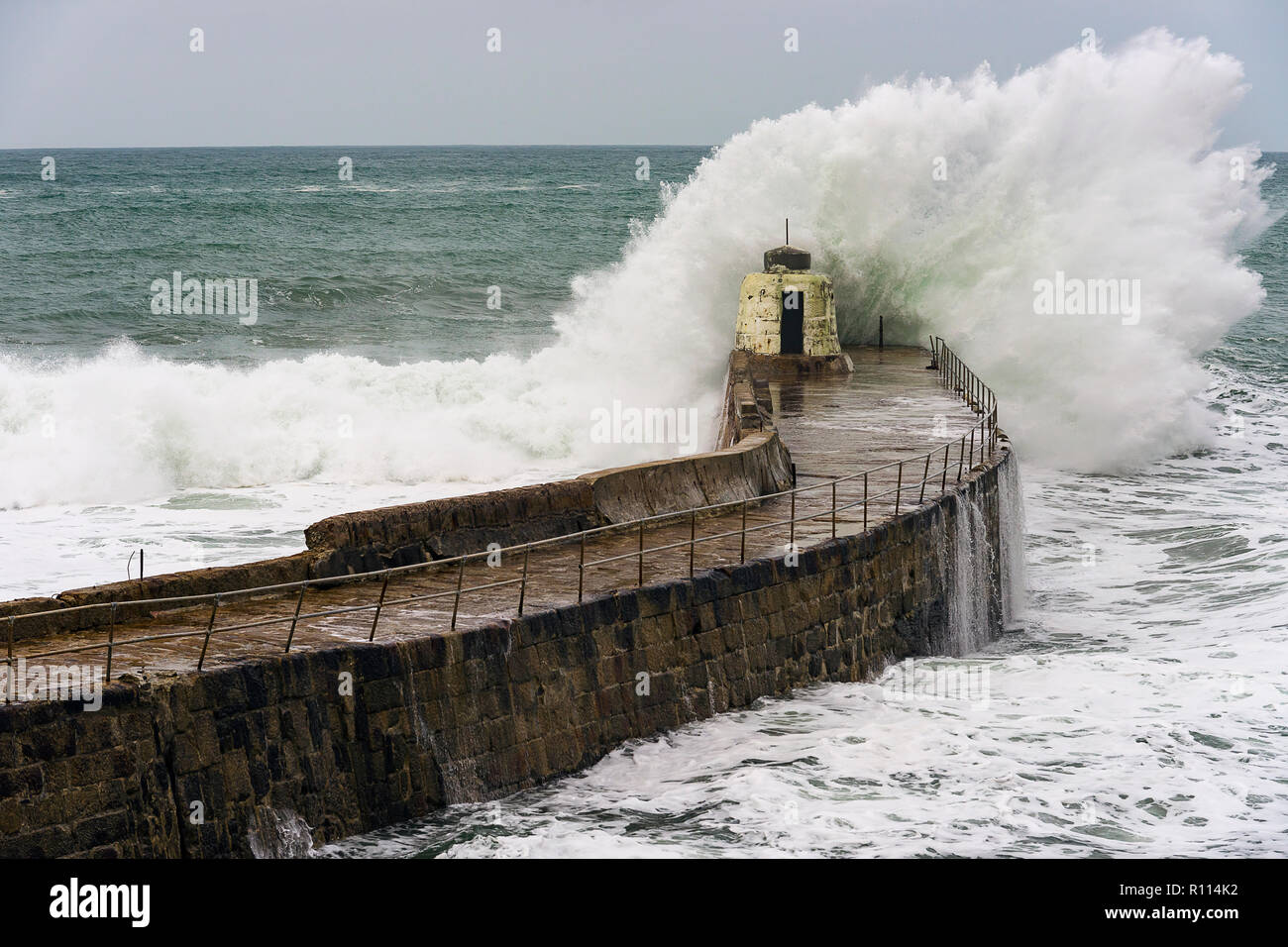 Portreath, Cornwall, UK. 04/11/2018. Gale force winds bring gigantic surf swells to Cornish harbour town of Portreath. - Stock Image
