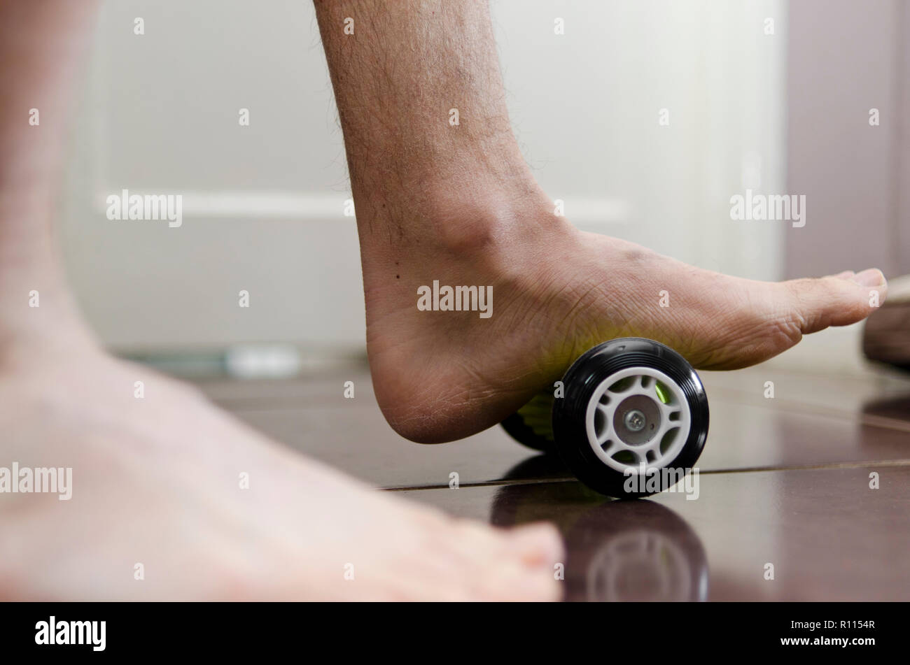 Plantar Fasciitis. Sufferer using a foot roller at home for treatment. Stock Photo