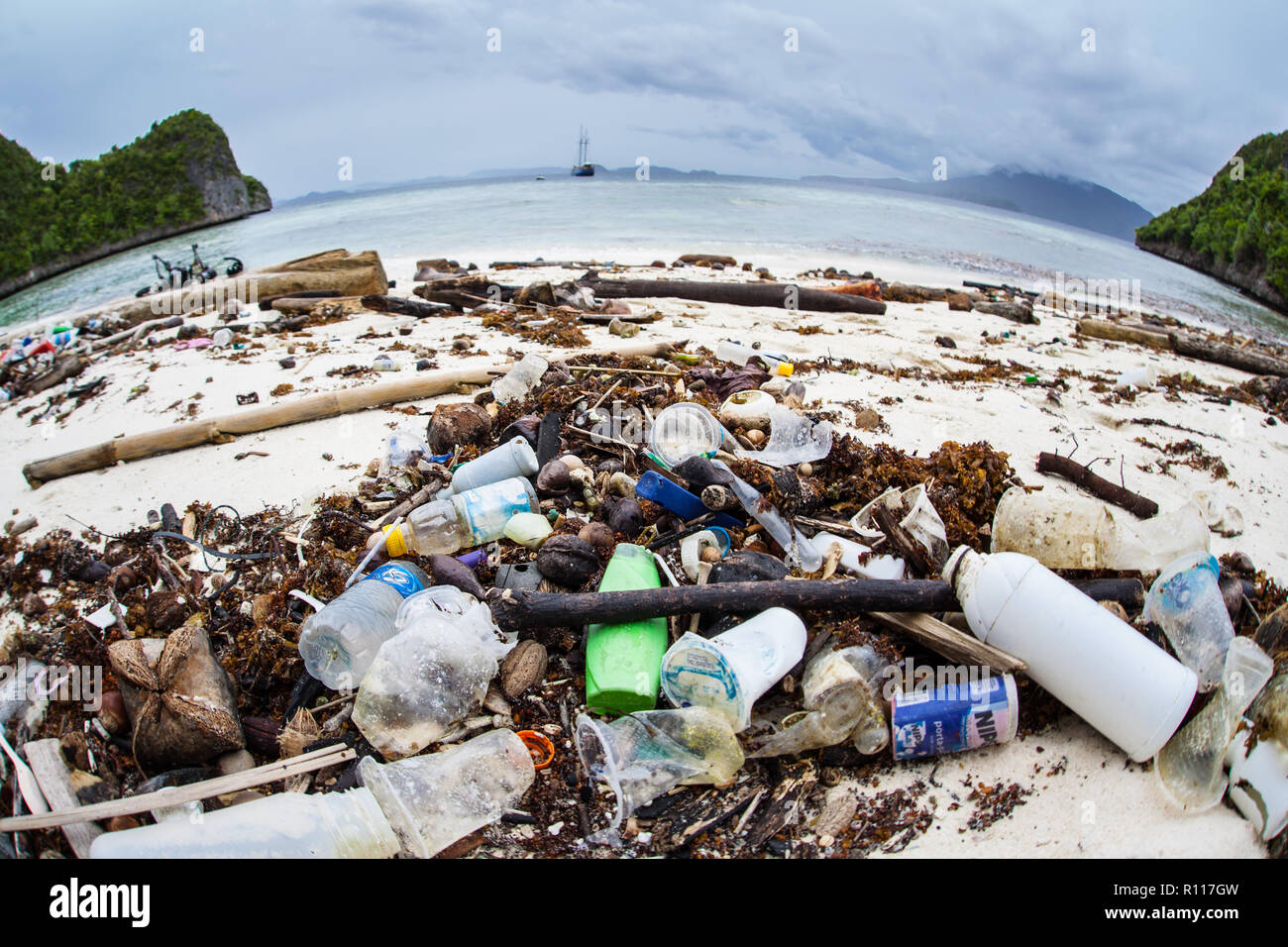 Discarded plastic bottles have washed up on a remote beach in Raja Ampat, Indonesia. Plastics break down into tiny pieces and enter the food chain. - Stock Image