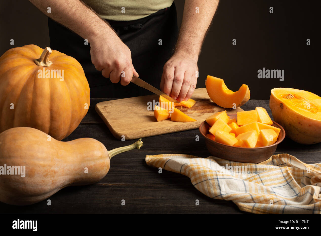The cook slices the pumpkin for baking. On a black wooden table are whole pumpkins of different sizes. - Stock Image