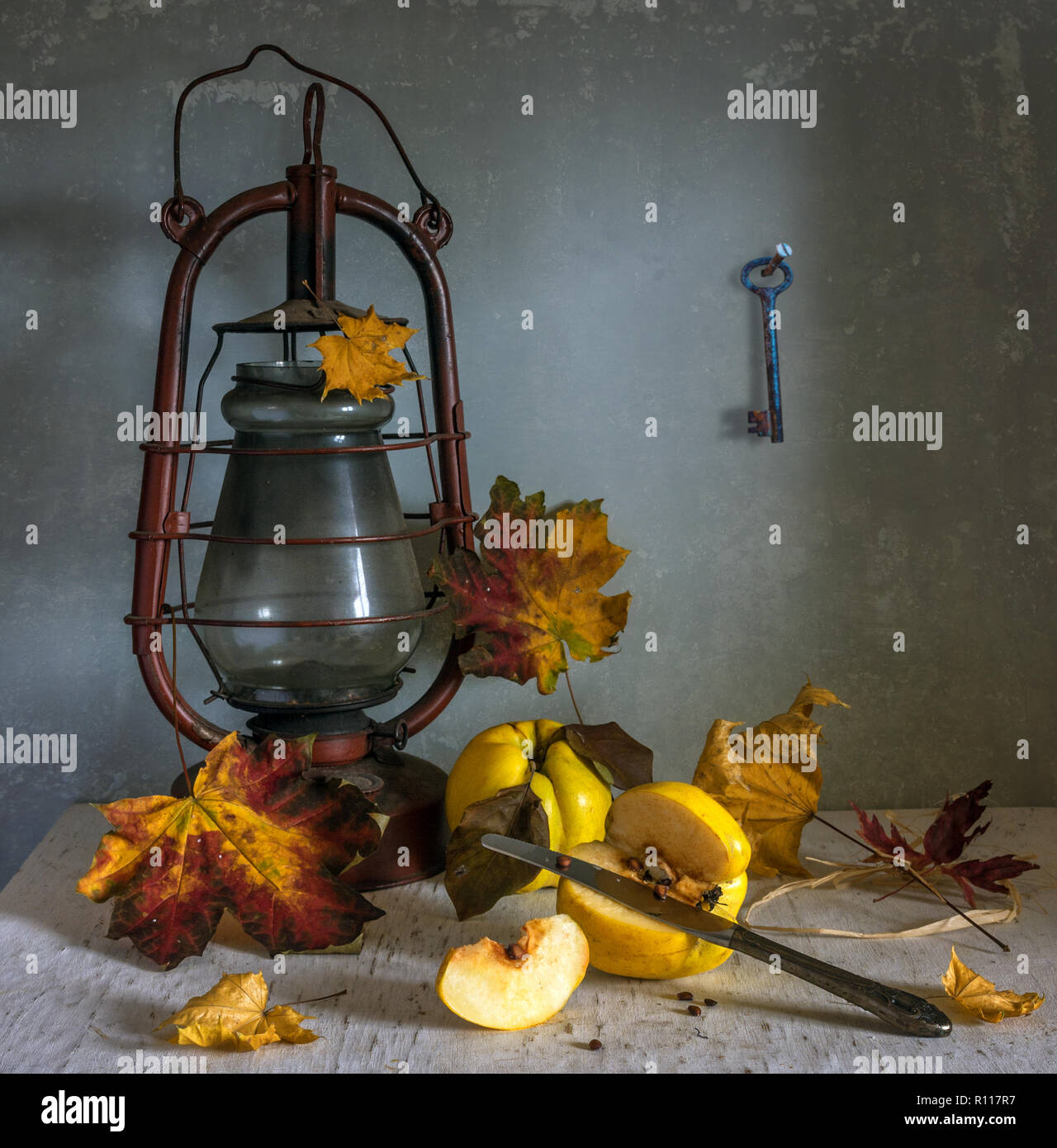 still life with quince, autumn leaves and kerosene lamp. vitamins. pick ripe fruit. vintage - Stock Image