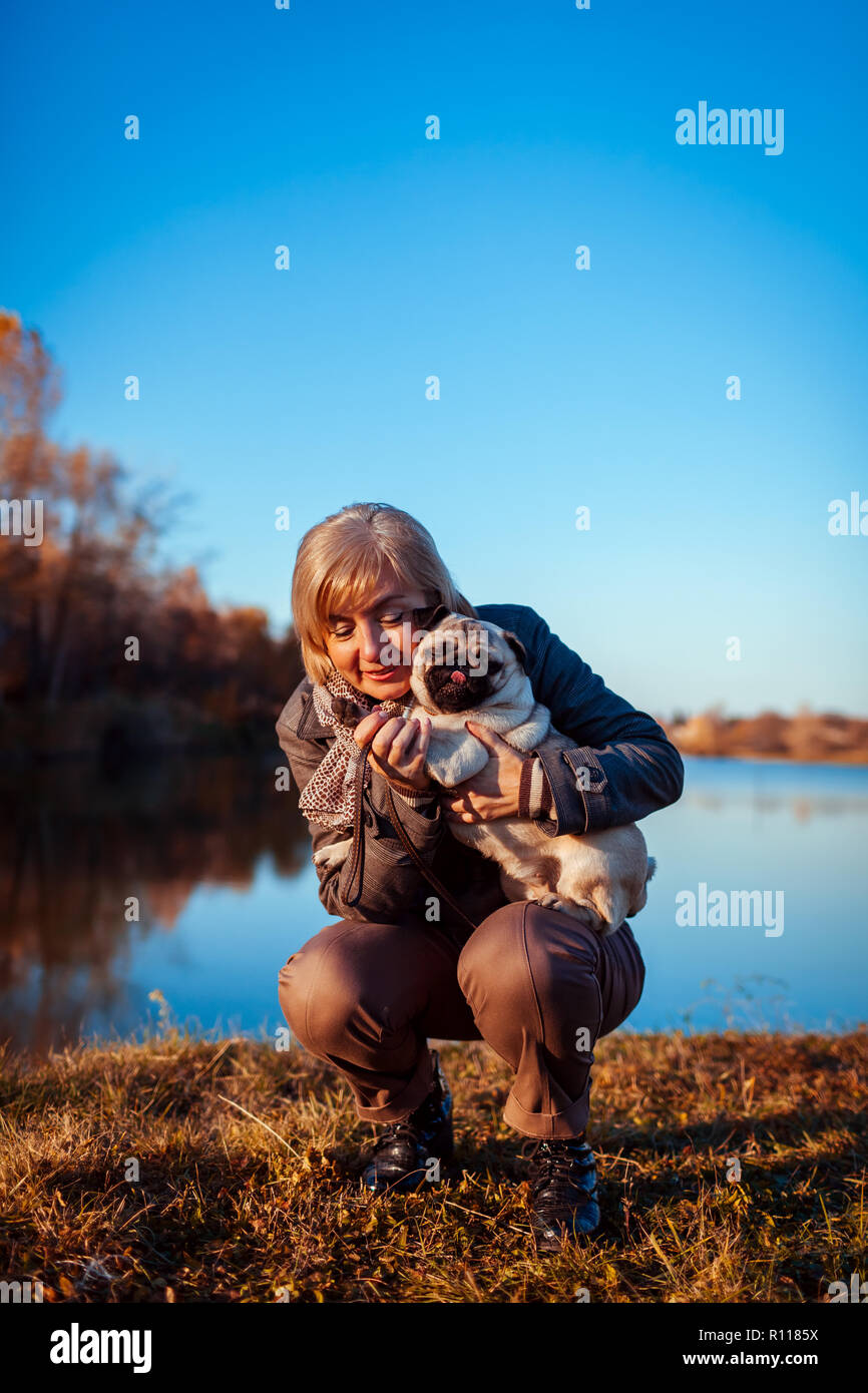 Master walking pug dog in autumn park by river. Happy woman hugging pet. - Stock Image