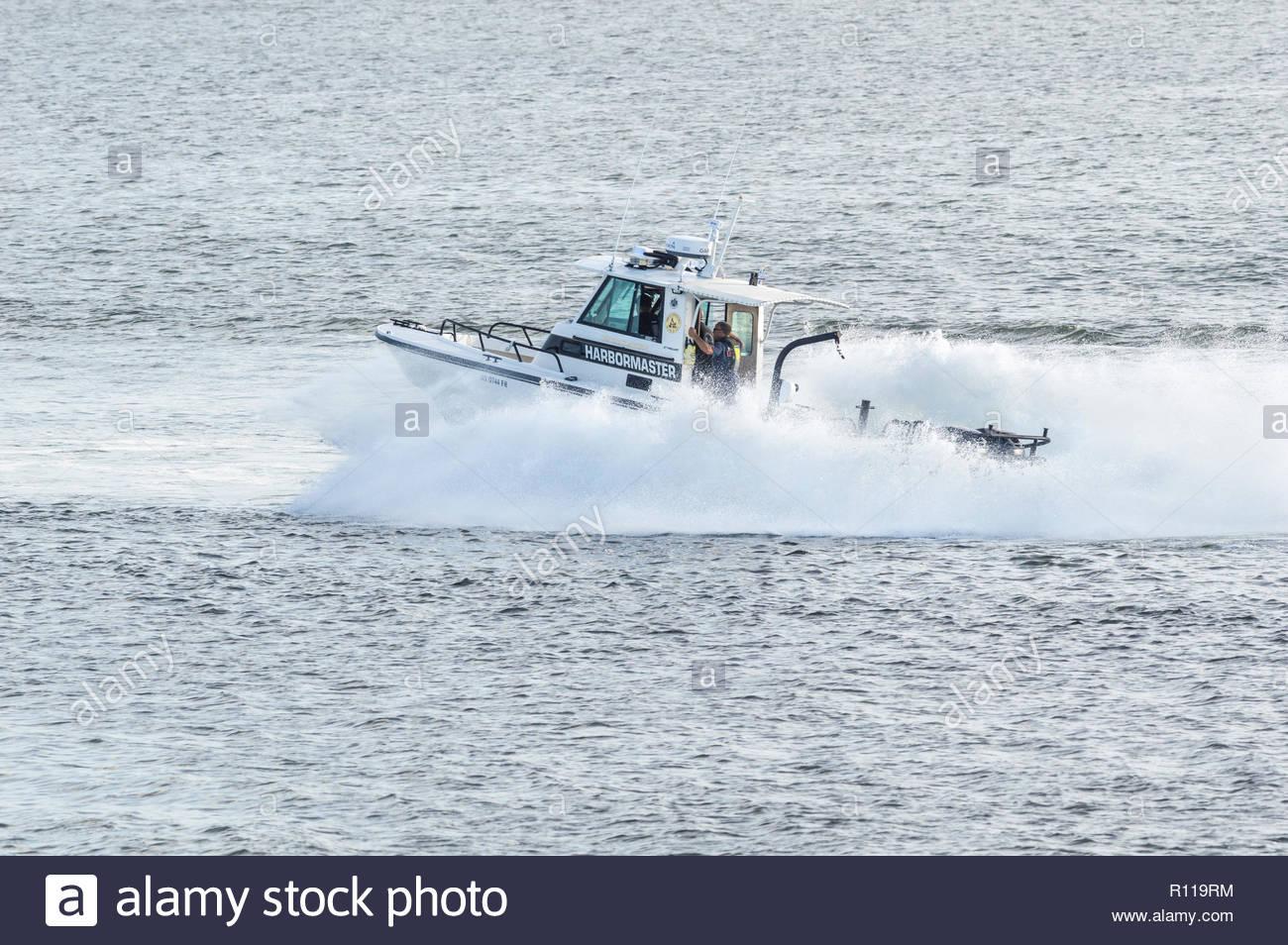 Fairhaven, Massachusetts, USA - August 31, 2018: Fairhaven harbormaster patrol boat smashing through wake of high-speed ferry - Stock Image