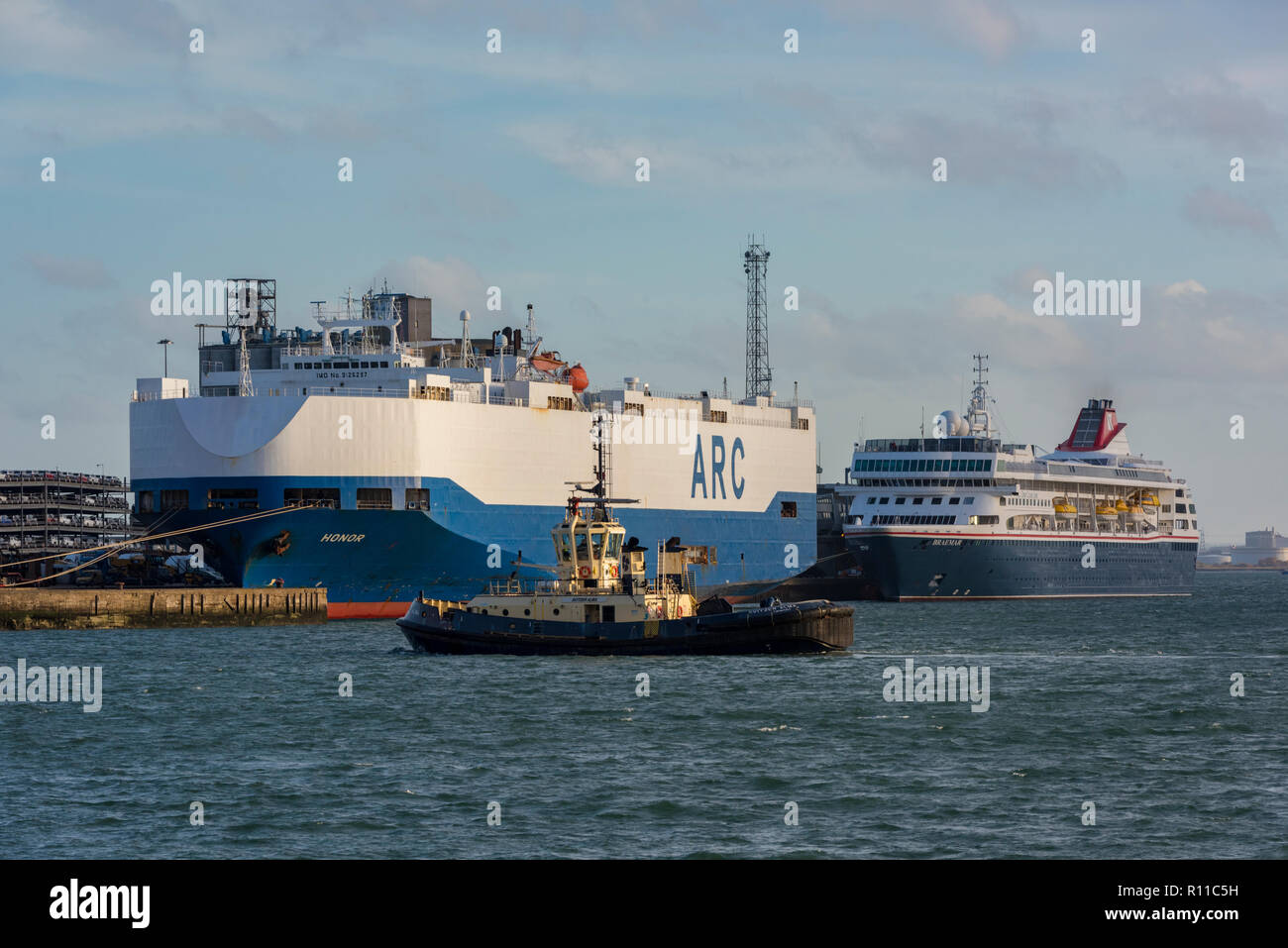 the Arc car carrier ship Honor next to the Fred Olsen cruise ship or liner Braemar and the Switzer tug Alma alongside in the port of southampton docks - Stock Image